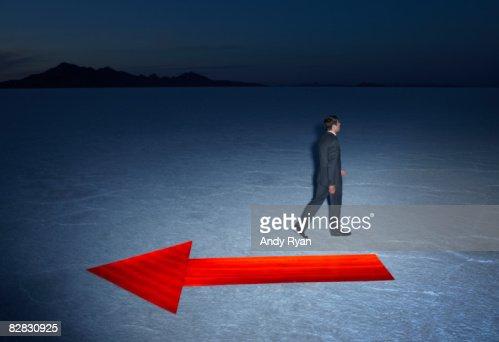 Man Walking Opposite Direction of Arrow, Salt Flat : Stock Photo
