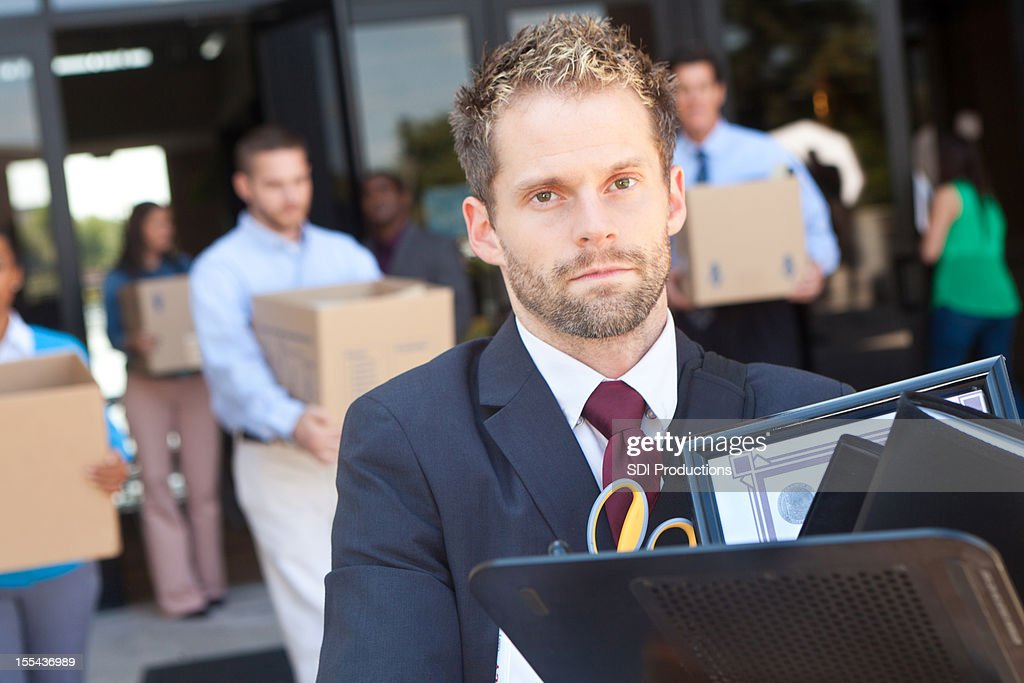 Man walking out of building with other laid off workers