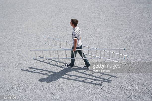 Man walking outdoors with two ladders