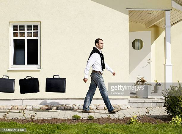 Man walking outside house, with three briefcases suspended in air behind (digital composite)
