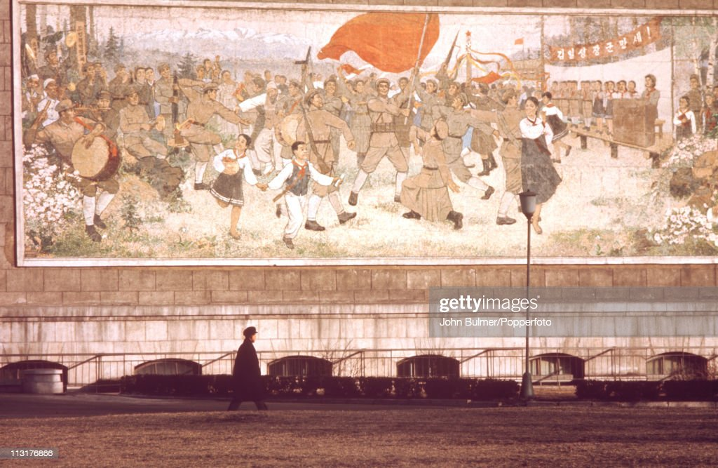 A man walking past a mural depicting the North Korean revolutionary struggle, North Korea, February 1973.