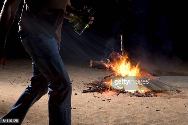 Man walking past bonfire on Hawaiian beach