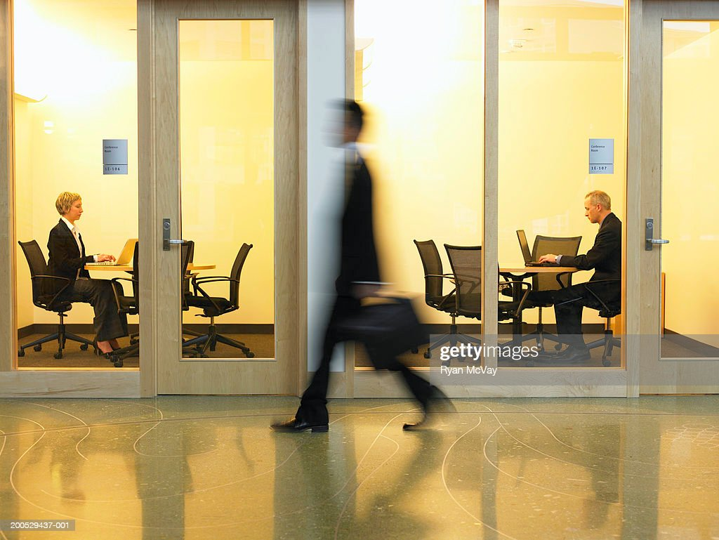 Man walking past executives using laptops in boardrooms, side view : Stock Photo