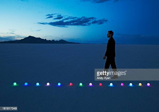 Man walking path of glowing orbs in desert.