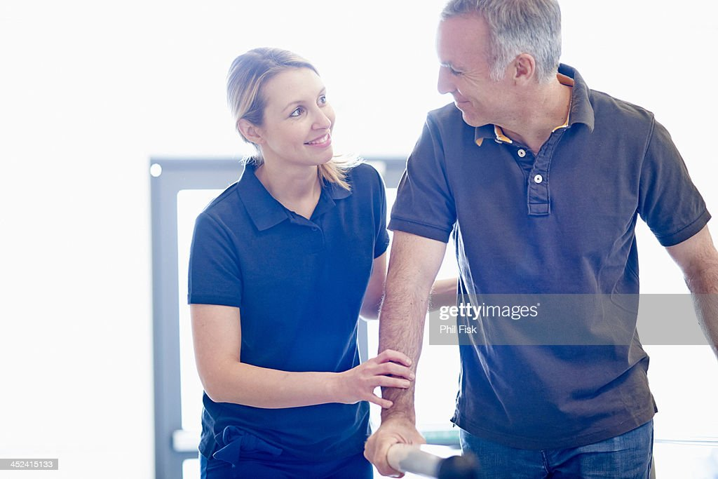Man walking supported by rails, guided by therapist