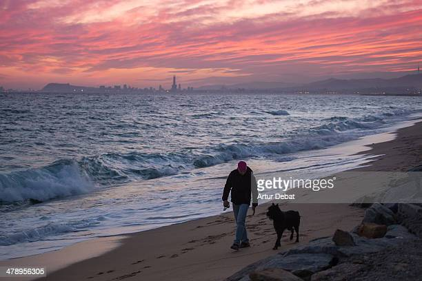 Man walking the dog at the beach with sunset and cityscape background