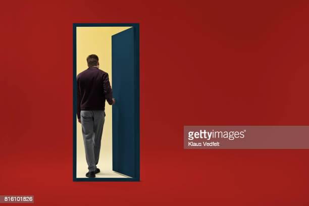 Man walking threw doorway in futuristic room