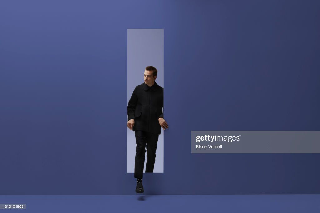 Man walking threw rectangular opening in coloured room : Stock Photo