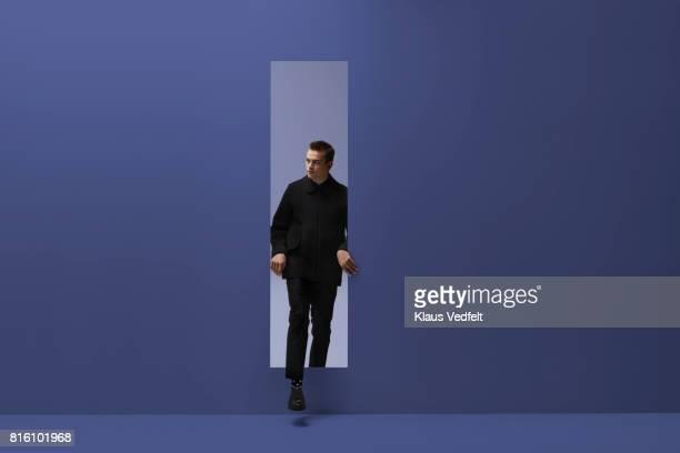 Man walking threw rectangular opening in coloured room