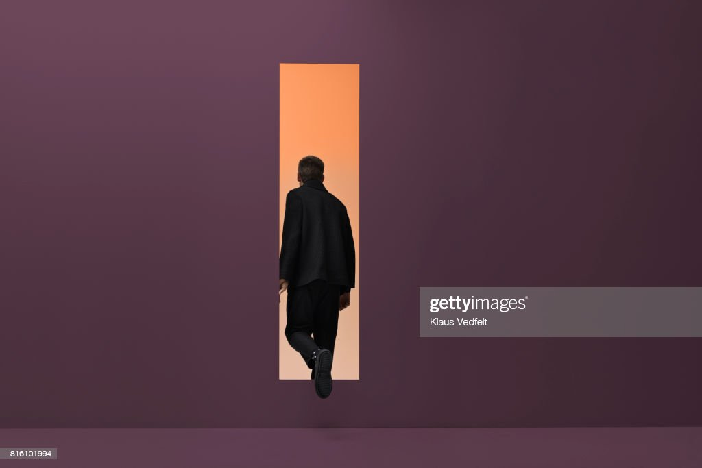Man walking threw rectangular opening in coloured room : Stock Photo