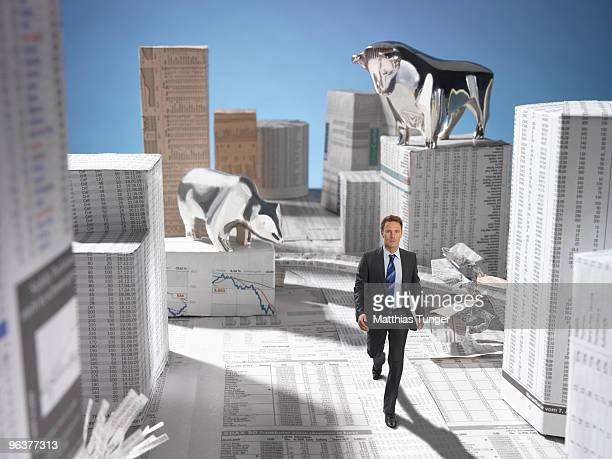 Man walking through a city made of newspaper