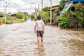 man walking through a flood on street