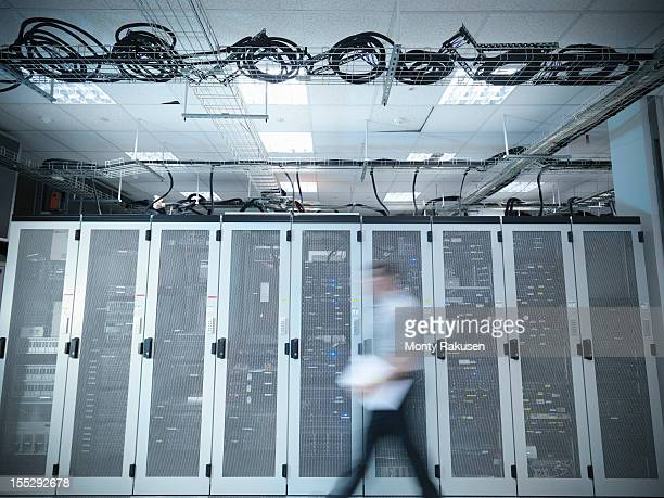 Man walking through computer server room, blurred motion