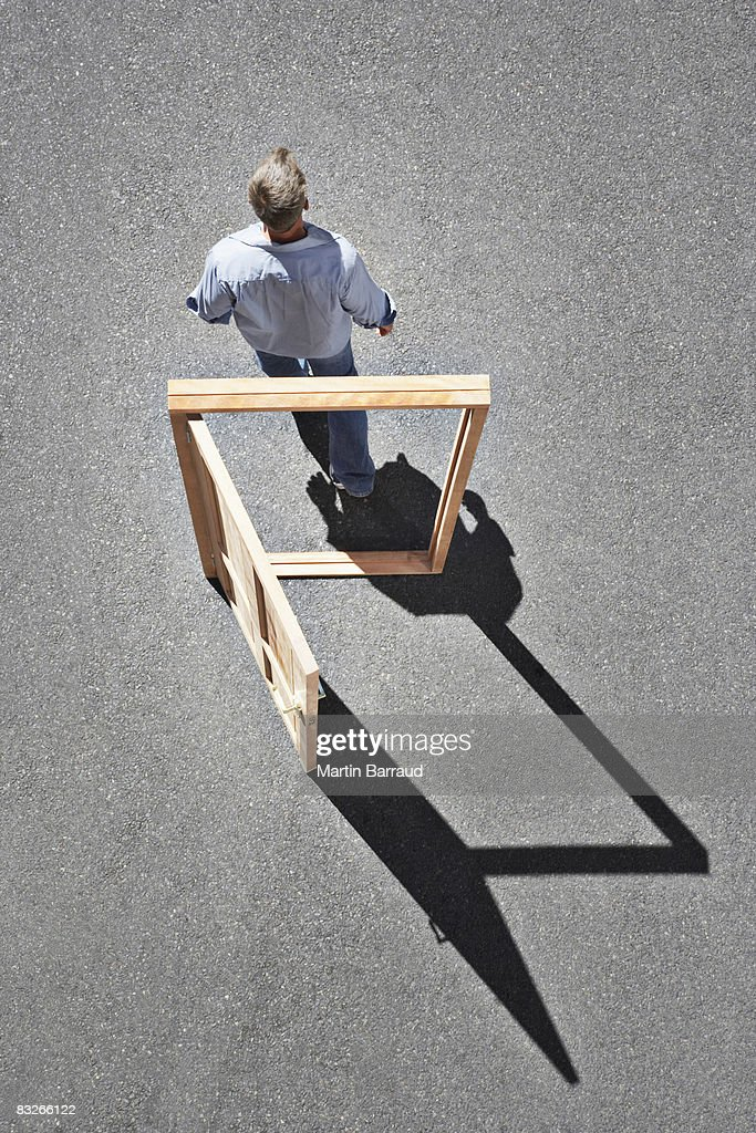 Man walking through door frame : Stock Photo