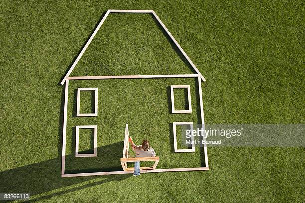 Man walking through door in house outline