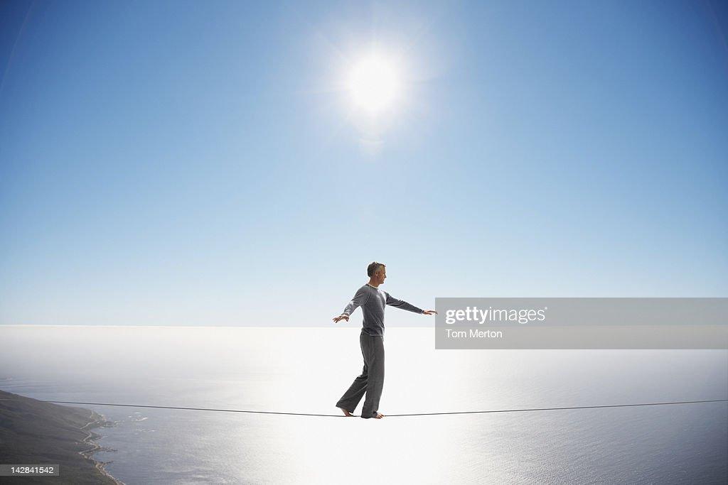 Man walking tightrope over still ocean