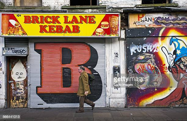 A man walking to work past shopfronts covered in graffiti on Brick Lane in the East End of London