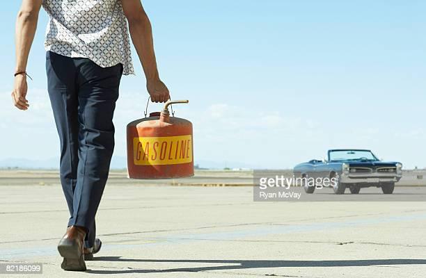 Uomo camminare in direzione auto con gas can