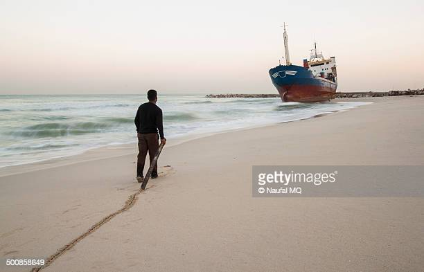 Man walking towards the grounded ship