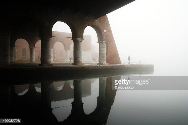 Man walking under arches in historic building in Venice in a foggy day