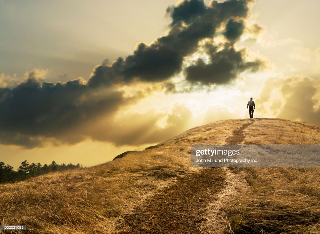 Man walking under dramatic clouds over grassy rural hill