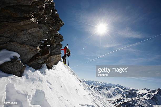 man walking up a mountain with skis