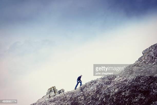 Man walking up a steep rock face
