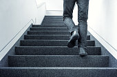 Man walking upstairs in modern interior. Blue colorized picture