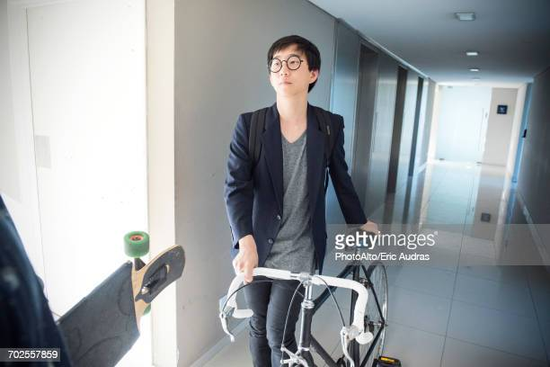 Man walking with bicycle in corridor