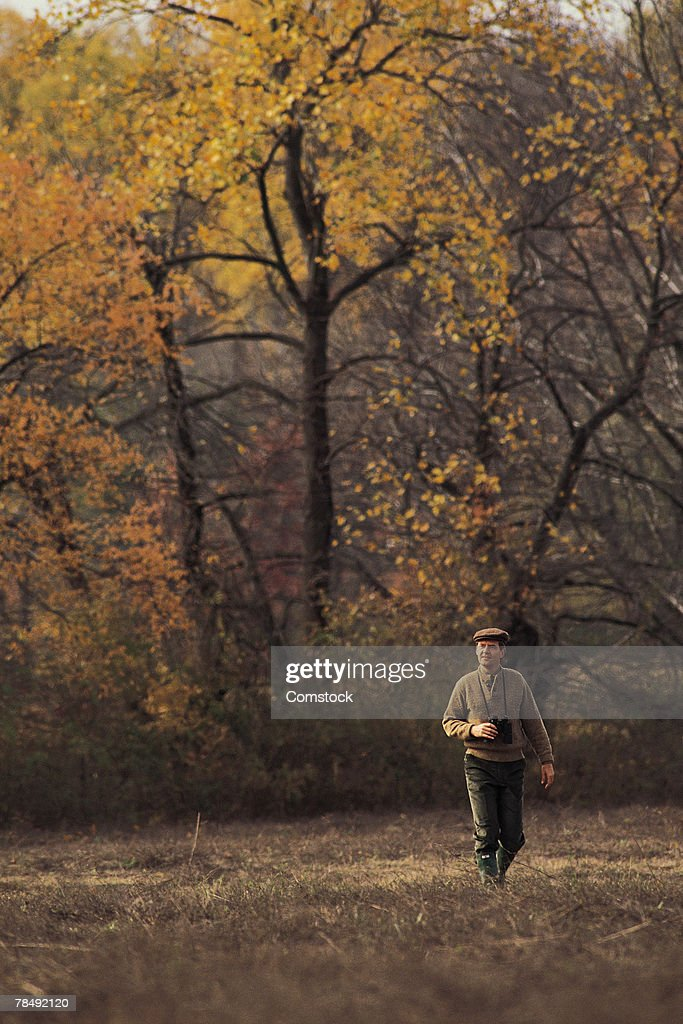 Man walking with binoculars : Stock Photo