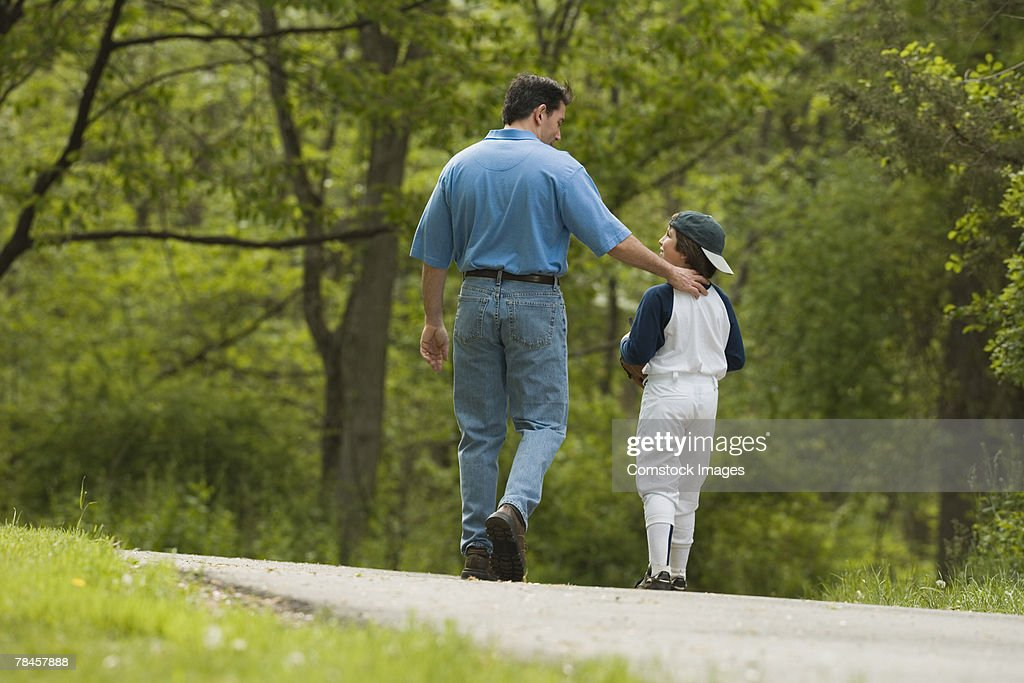 Man walking with boy in baseball uniform : Stock Photo