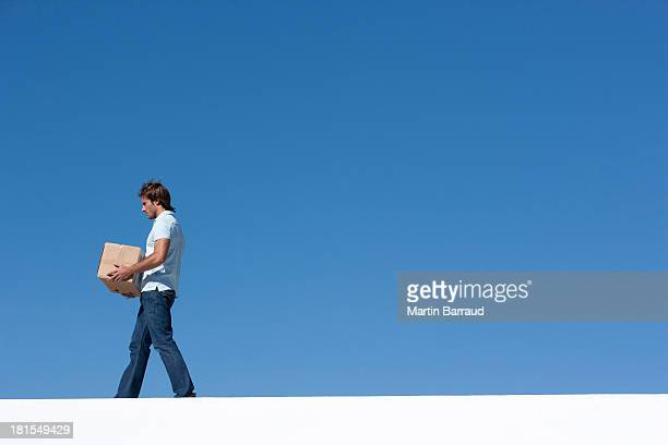 Man walking with cardboard box outdoors with blue sky