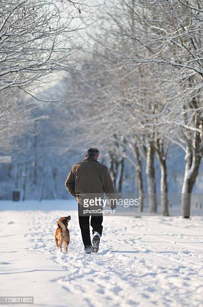 Man walking with dog in winter park