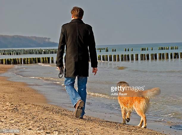 Man walking with dog on sunny beach