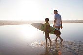 Man walking with grandson carrying surf board