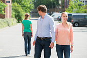 Young Man Walking With His Girlfriend On Street Looking At Another Woman