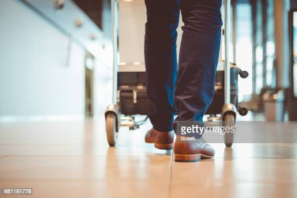 Man walking with luggage trolley in airport terminal