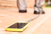 Man walking with smartphone chained to his leg Conceptual picture for internet addiction