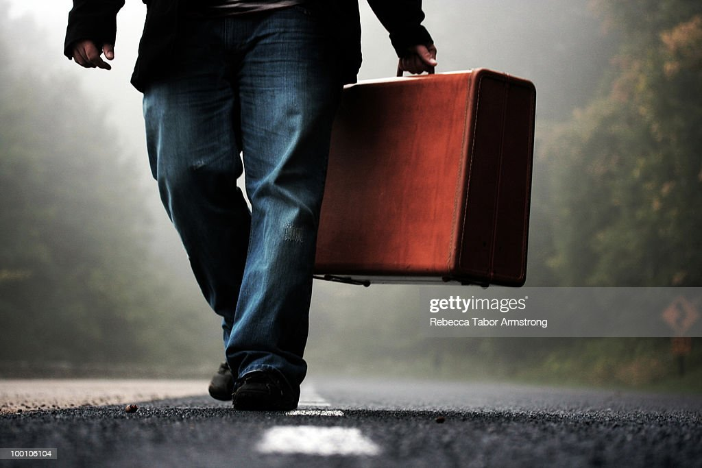 Man walking with suitcase in early morning fog. : Stock Photo