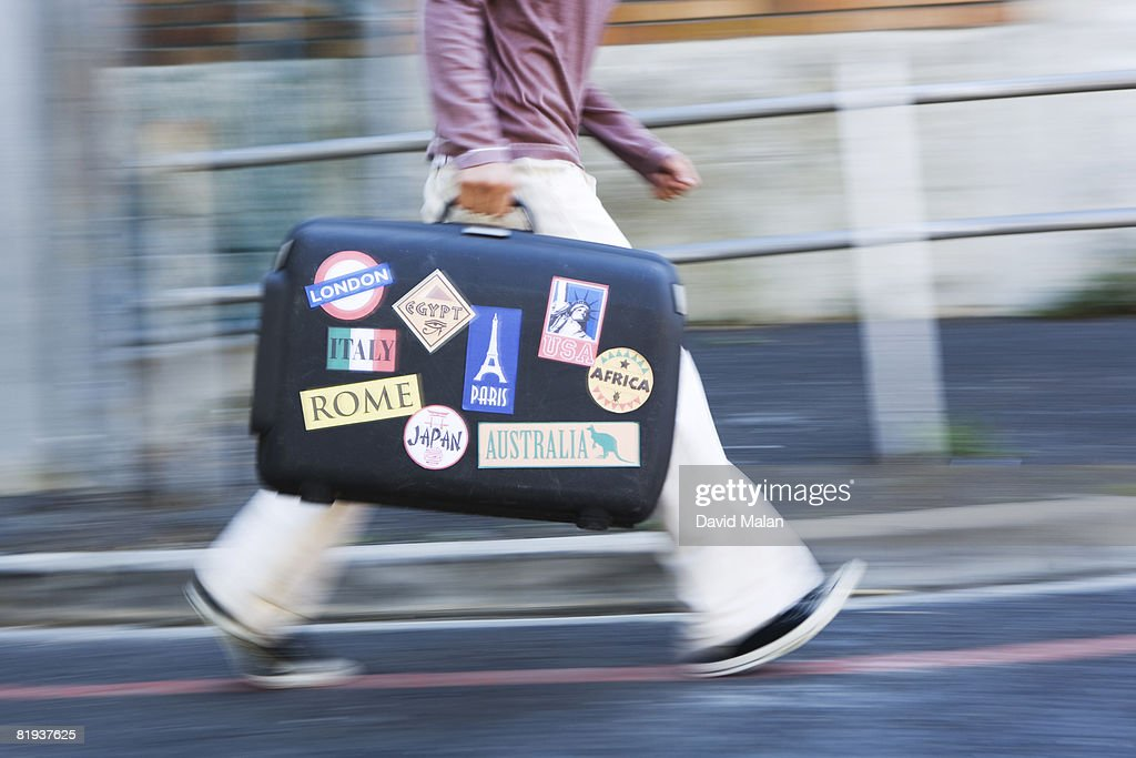 Man walking with suitcase with stickers from countries : Stock Photo