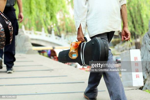 Man Walking With Violin On Its Case