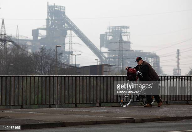 A man walks a bike past the ThyssenKrupp steelworks on April 4 2012 in Duisburg Germany The city of Dortmund is located in the traditionally...