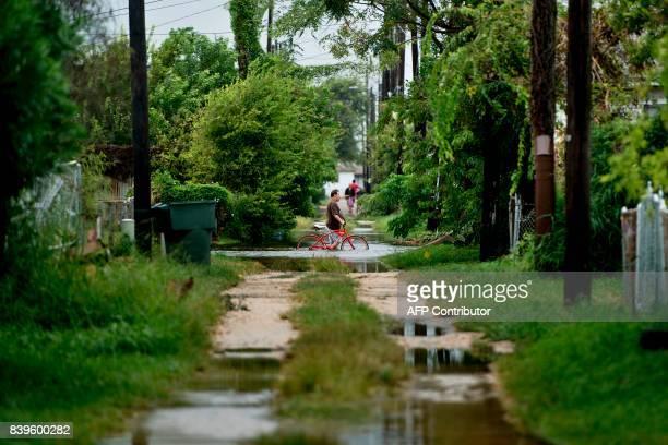 A man walks a bike through a flooded street as the effects of Hurricane Harvey are seen August 26 2017 in Galveston Texas Hurricane Harvey left a...
