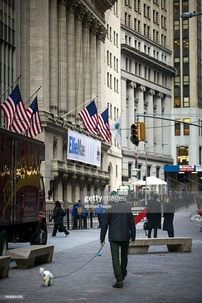A man walks a dog in front of the New York Stock Exchange on February 4, 2013 in New York City. Stocks dropped sharply today following the Dow's close last week above 14000.