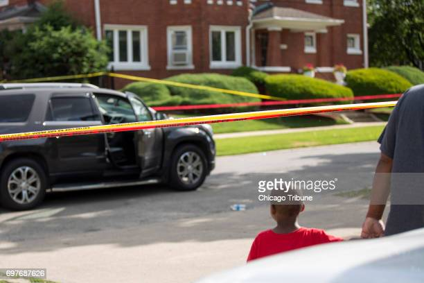 A man walks a young boy past the scene of a shooting on the 600 block of East 82nd Street Sunday June 18 in the Chatham neighborhood of Chicago A...