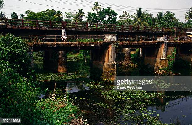 'A man walks accross a bridge over the backwaters in Ayamenam in Kerala near Aymenam the village where Arundhati Roy set her Book Prize winning novel...