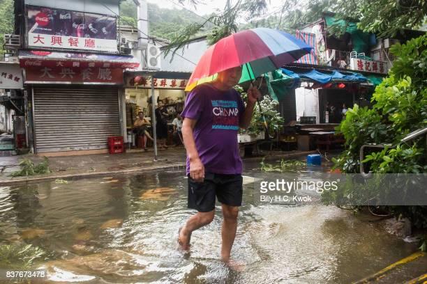 A man walks across a flooded street as Typhoon Hato hits Hong Kong on August 23 2017 in Hong Kong Hong Kong Hong Kong's weather authorities raised...