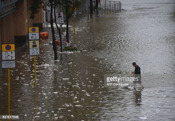 TOPSHOT A man walks across a flooded street in the Heng Fa Chuen area as Typhoon Hato hits Hong Kong on August 23 2017 Heavy rains and driving winds...