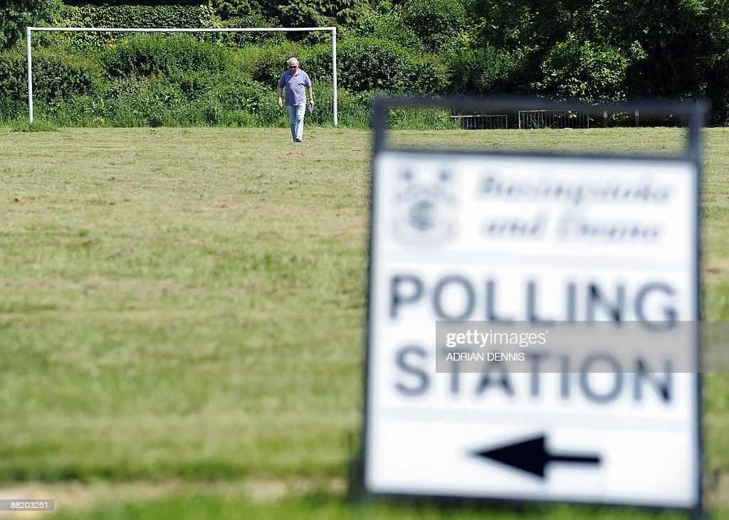 A man walks across a football field to cast a vote at a polling station in the Village Hall in North Waltham in Hampshire an outlying village in the...