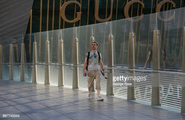 A man walks across a pedestrian bridge from The Crystals luxury shopping mall part of the CityCenter complex on May 31 2017 in Las Vegas Nevada...